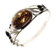 White metal hinged bangle of foliate design with large central amber-coloured cabochon, stamped 925