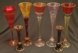 A collection of five coloured patterned stemmed glasses together with a pair of smaller coloured