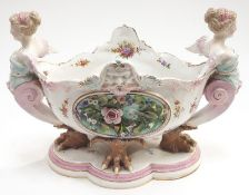 A porcelain Dresden style table centrepiece with claw feet flanked on either side by two ladies.