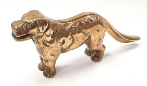 A solid brass anrique nut cracker in the form of a dog.
