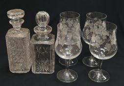 A set of four drinking glasses together with two crystal glass decanters.