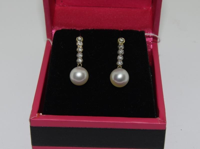 A pair of white gold diamond and cultured pearl drop earrings.