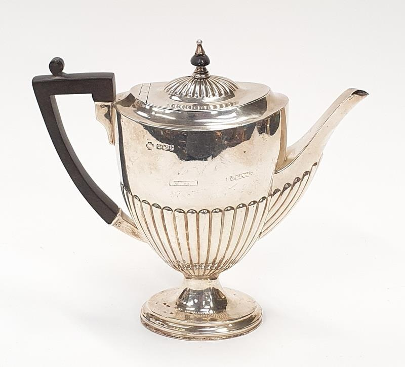 A solid silver tea pot with fluted design and Bakelite handle. 380gm