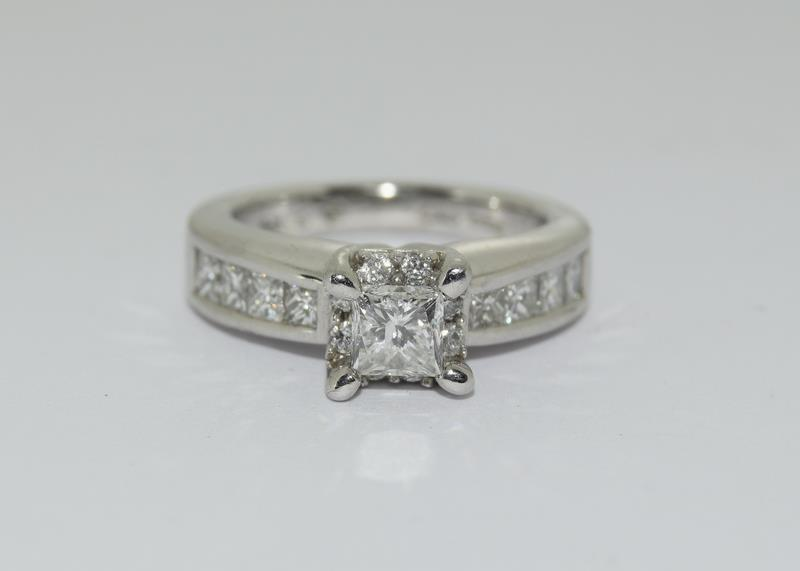 A 14ct white gold and diamond ring with central princess cut diamond. Size K