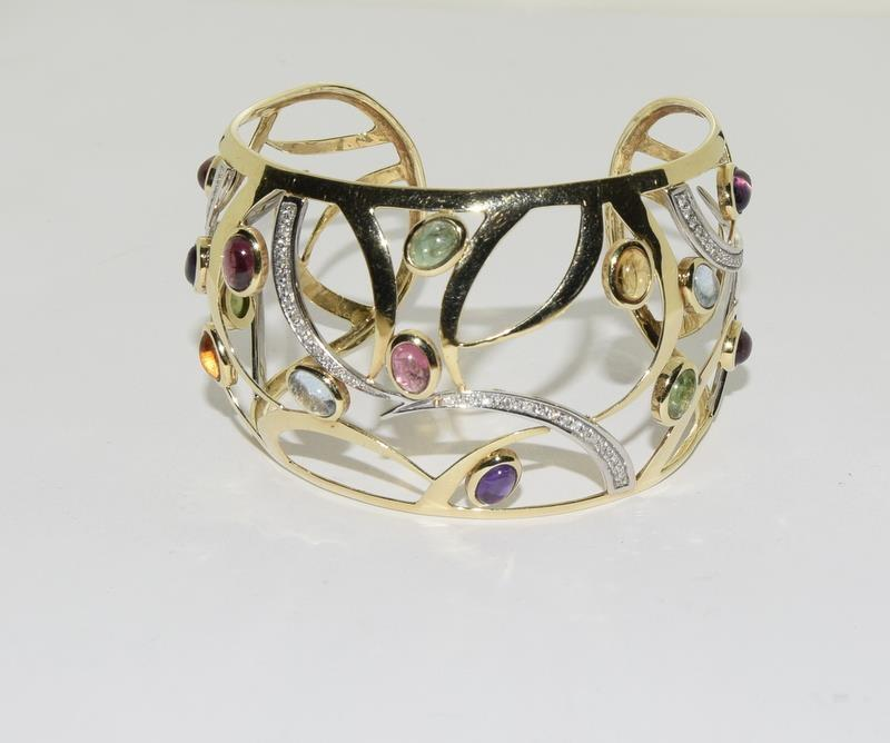 A 14ct yellow gold bangle set with diamonds, citrines, peridot etc.
