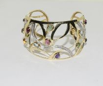 A 14ct yellow gold bangle set with diamonds, citrines, peridot etc.