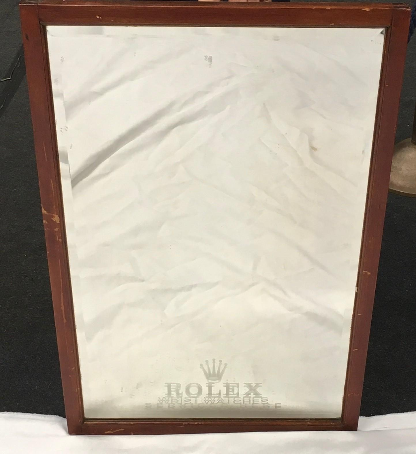 A wood framed and bevel edged mirror, etched Rolex. 80 cm by 53 cm