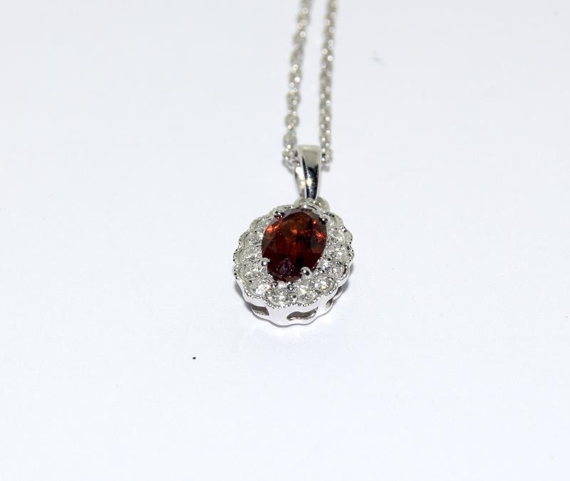 An 18ct white gold garnet and diamond pendant necklace.