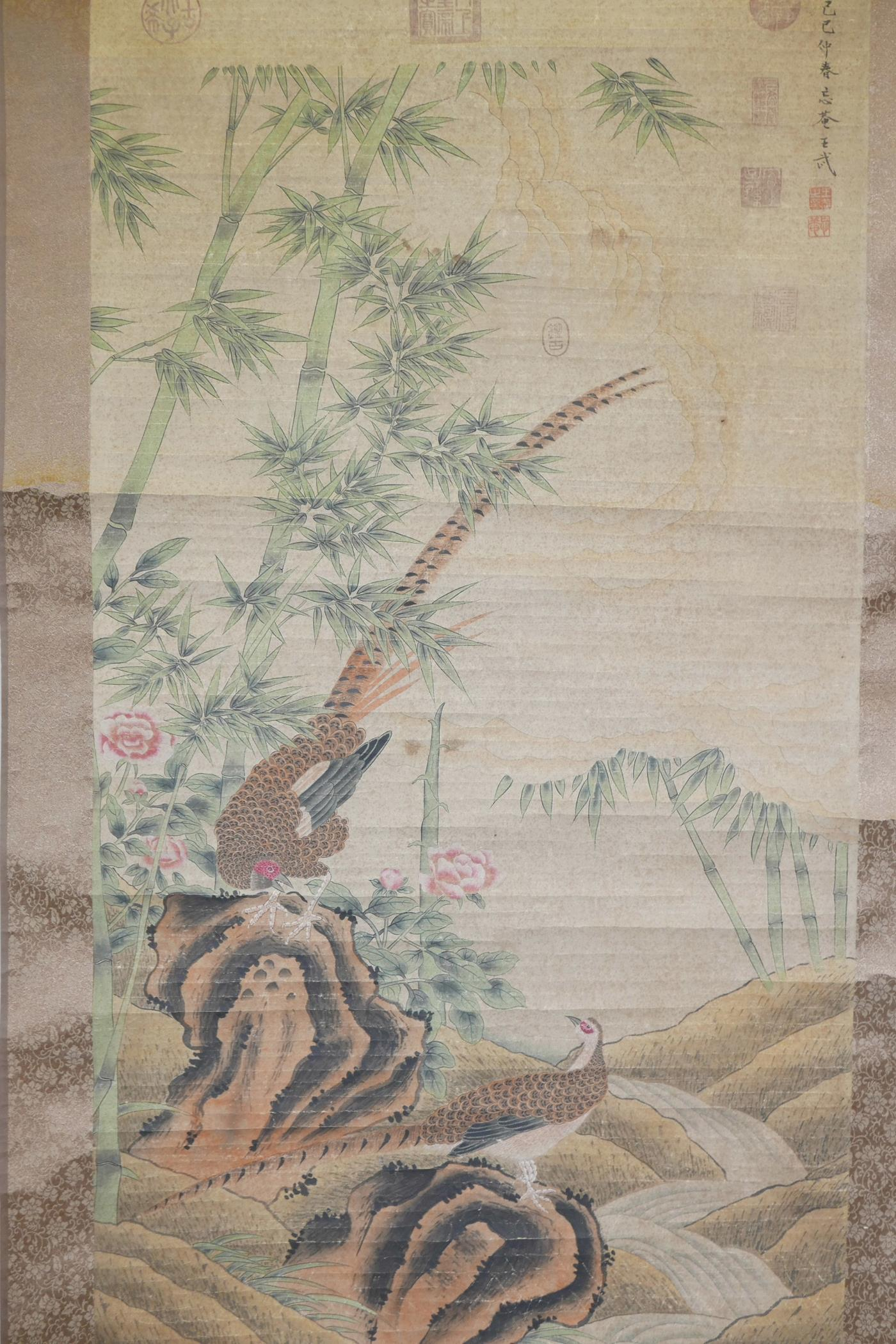 """Lot 28 - A Chinese watercolour scroll decorated with two pheasants in a landscape, 26"""" x 49"""""""
