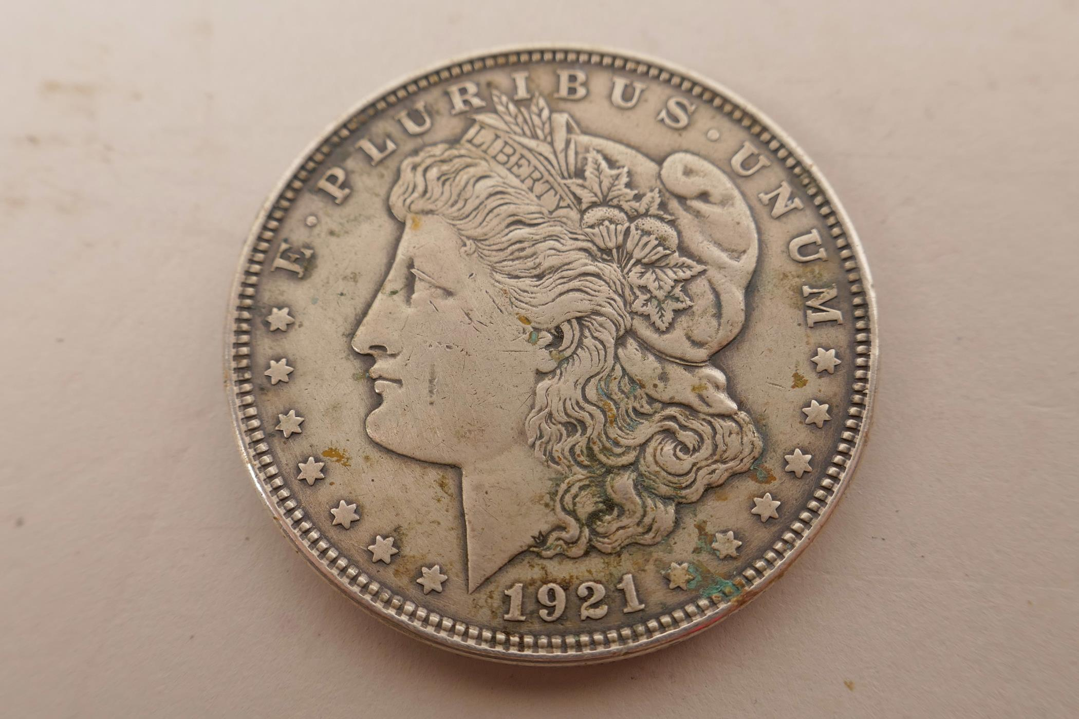 Lot 23 - A USA silver Morgan dollar coin minted in Philadelphia and dated 1921; a USA silver Kennedy 1964