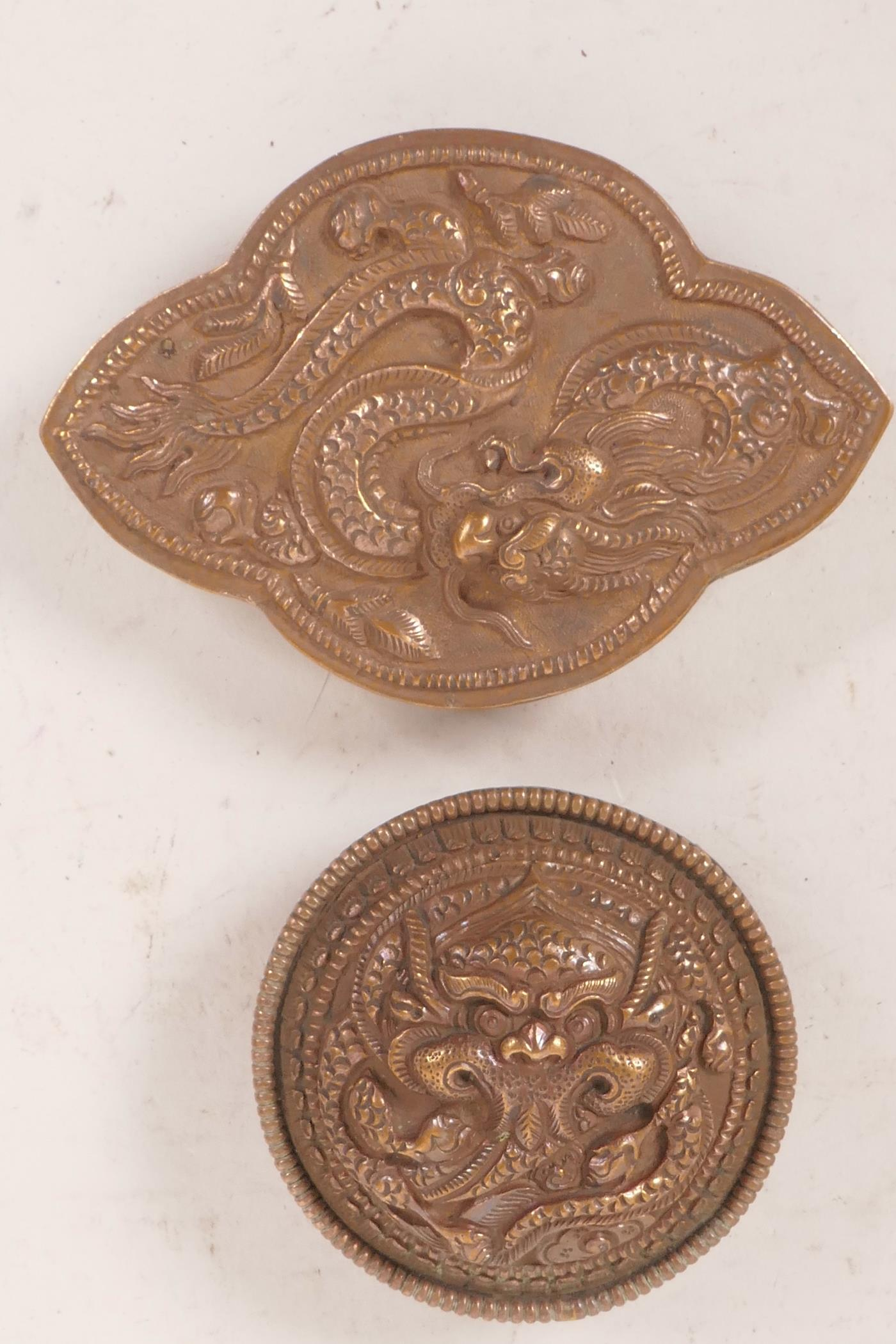 "Lot 2 - Two Chinese copper belt buckles, embossed with fiery dragons, largest 4"" x 2½"""