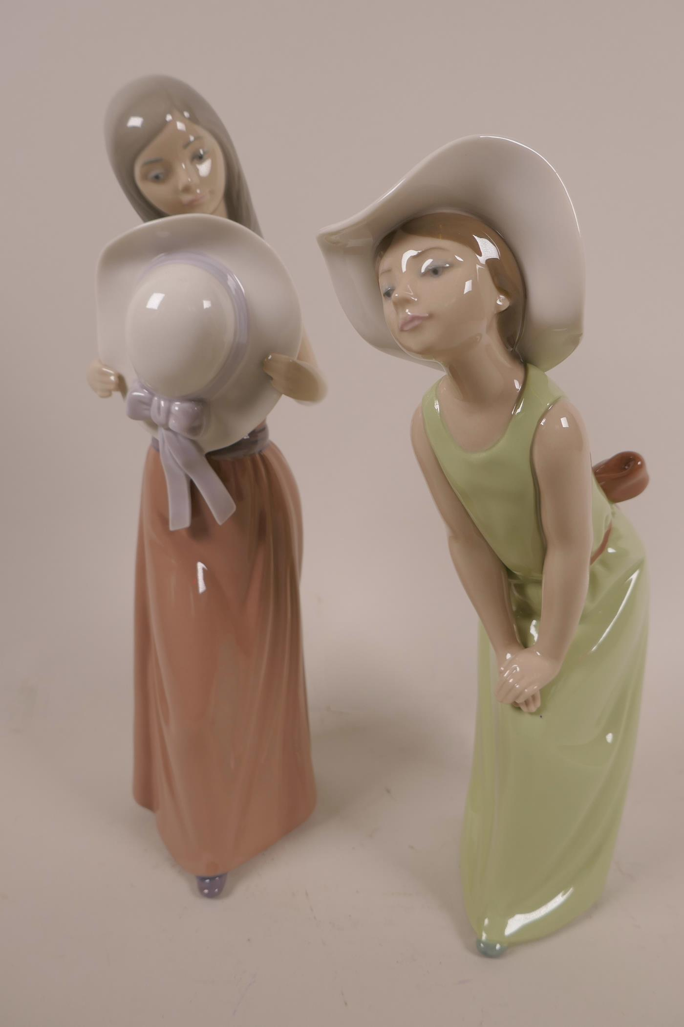 Lot 11 - Two Lladro figurines, 'Curious Girl with Straw Hat', #5009, and the other 'Bashful Girl with Straw