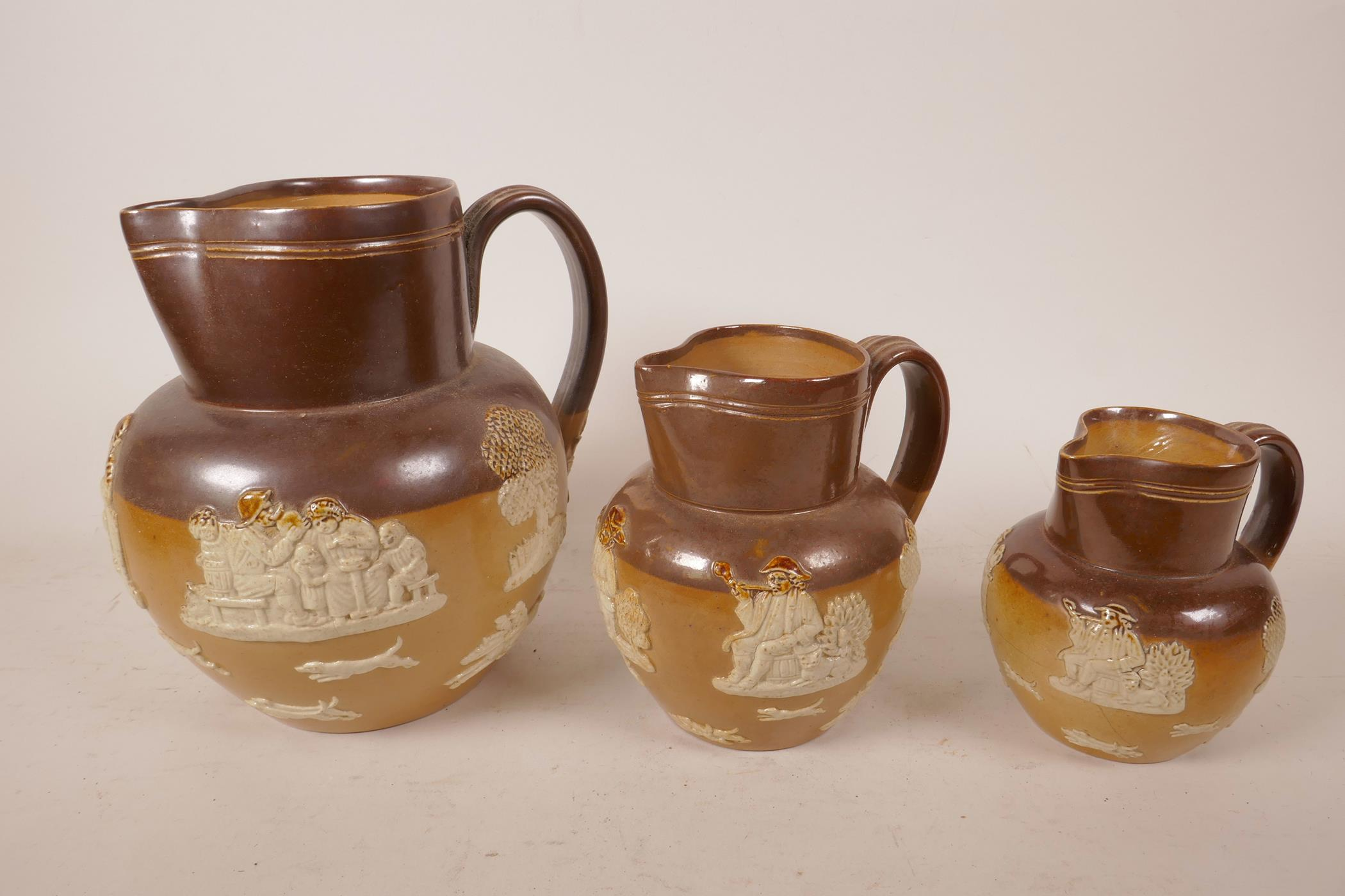 Lot 34 - Three Royal Doulton Lambeth stoneware jugs with farming scenes, circa 1905, various sizes, largest