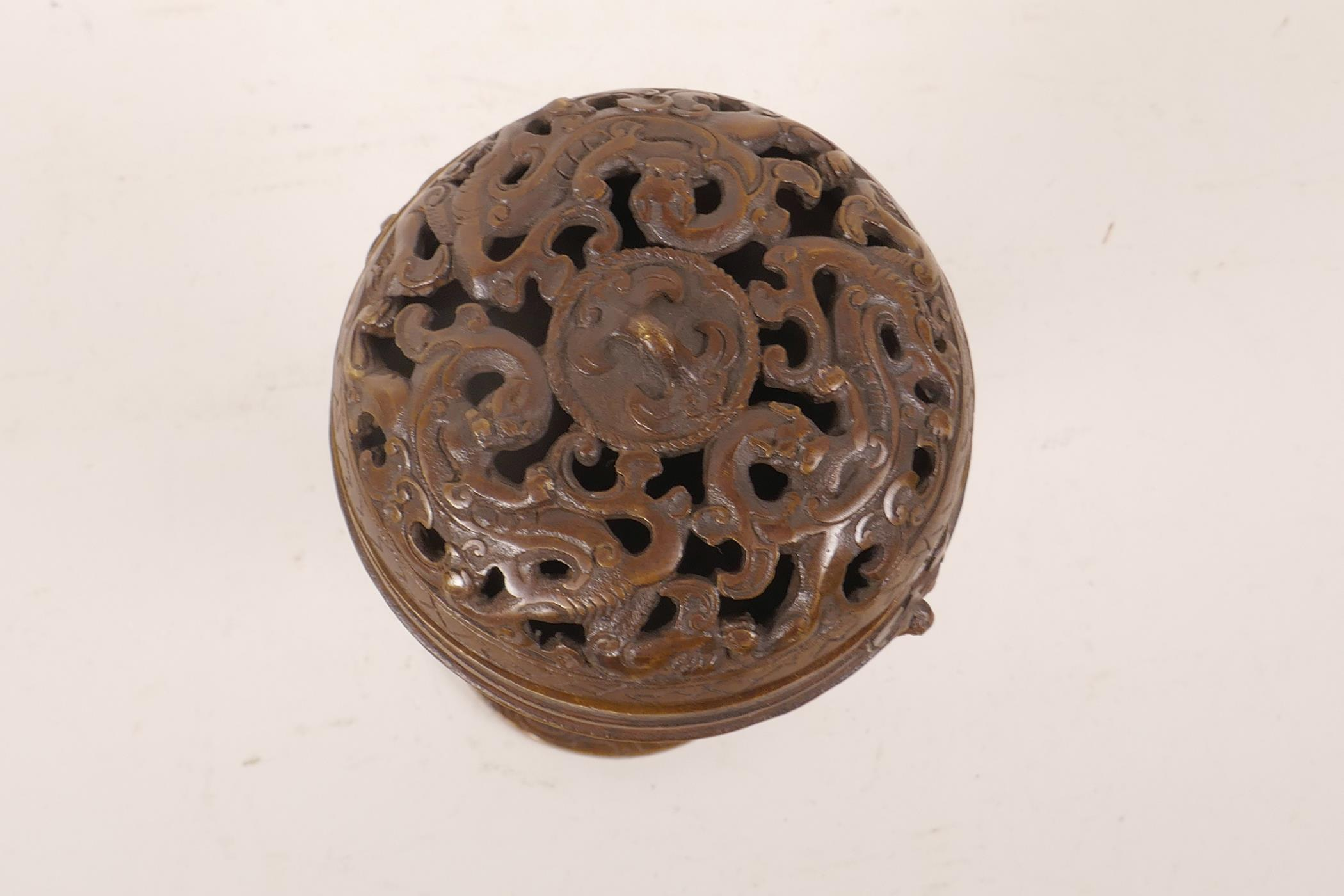 "Lot 8 - A Chinese bronze ball censer with pierced dragon decoration to cover, 6"" high"