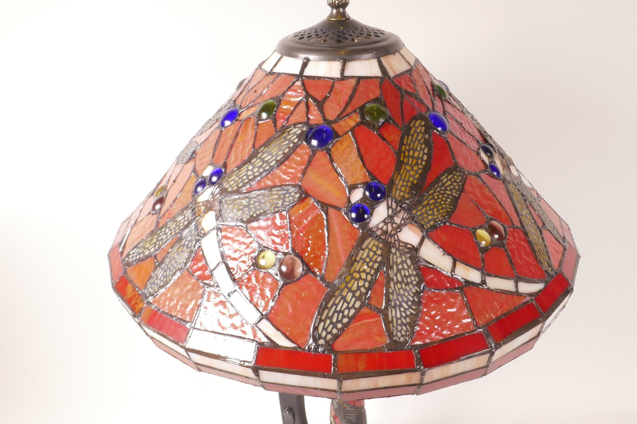 """Lot 32 - A Tiffany style table lamp with dragonfly decoration on a red ground, 21"""" high"""