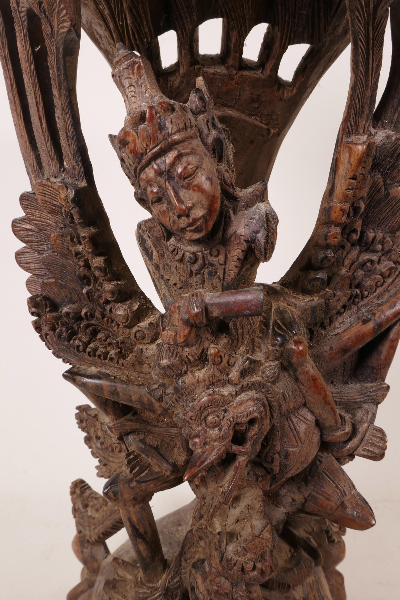 "Lot 16 - A 1940s Balinese hard wood carving of Vishnu riding Garuda, beautifully carved, A/F, 15"" high x 6"""