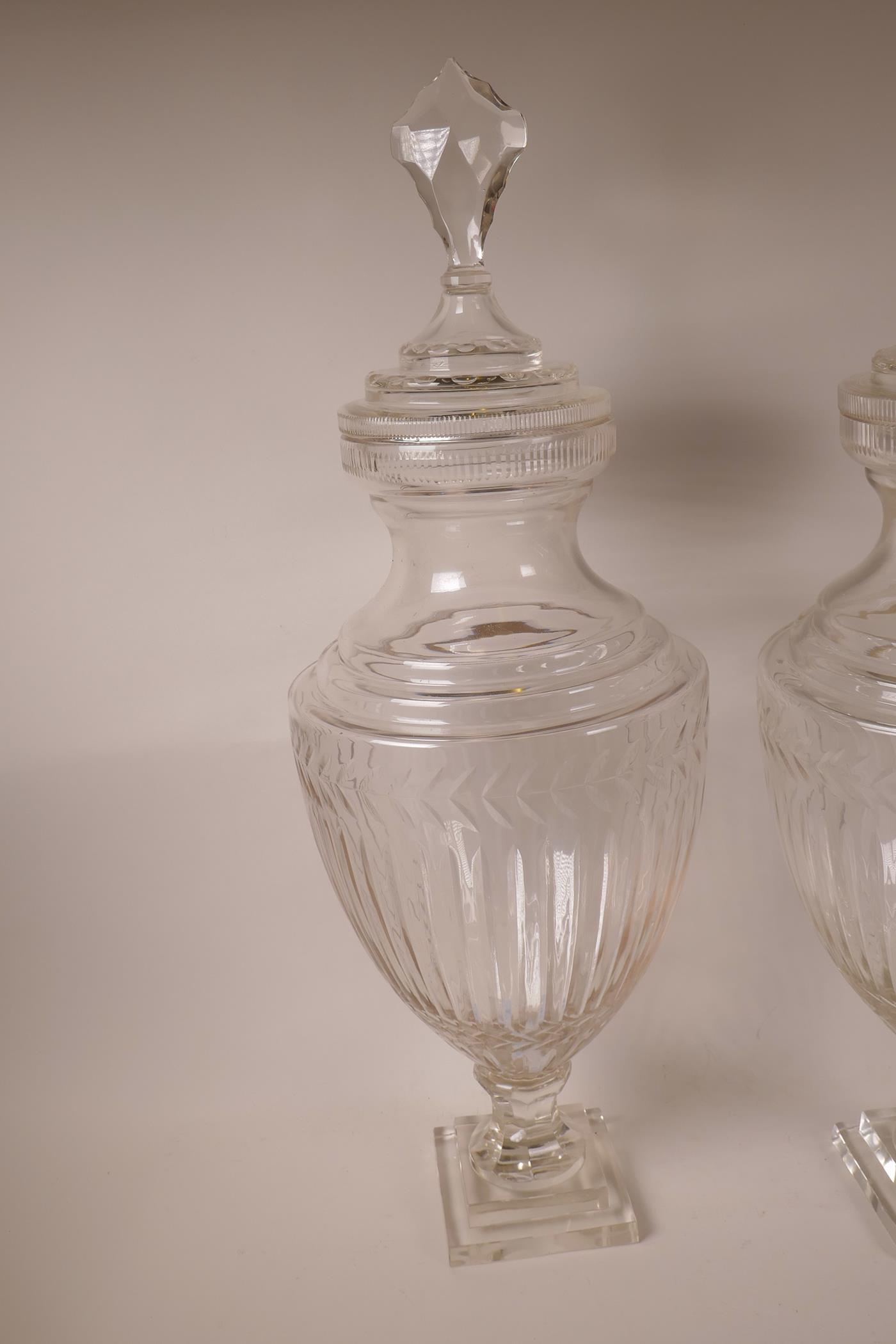 "Lot 57 - A pair of large glass pedestal urns and covers of baluster form, on a square pedestal base, 28"" high"