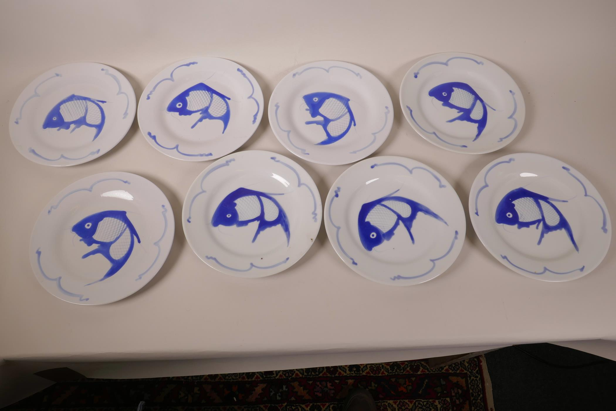 """Lot 38 - A set of eight Oriental blue and white porcelain side plates decorated with fish, 8"""" diameter"""