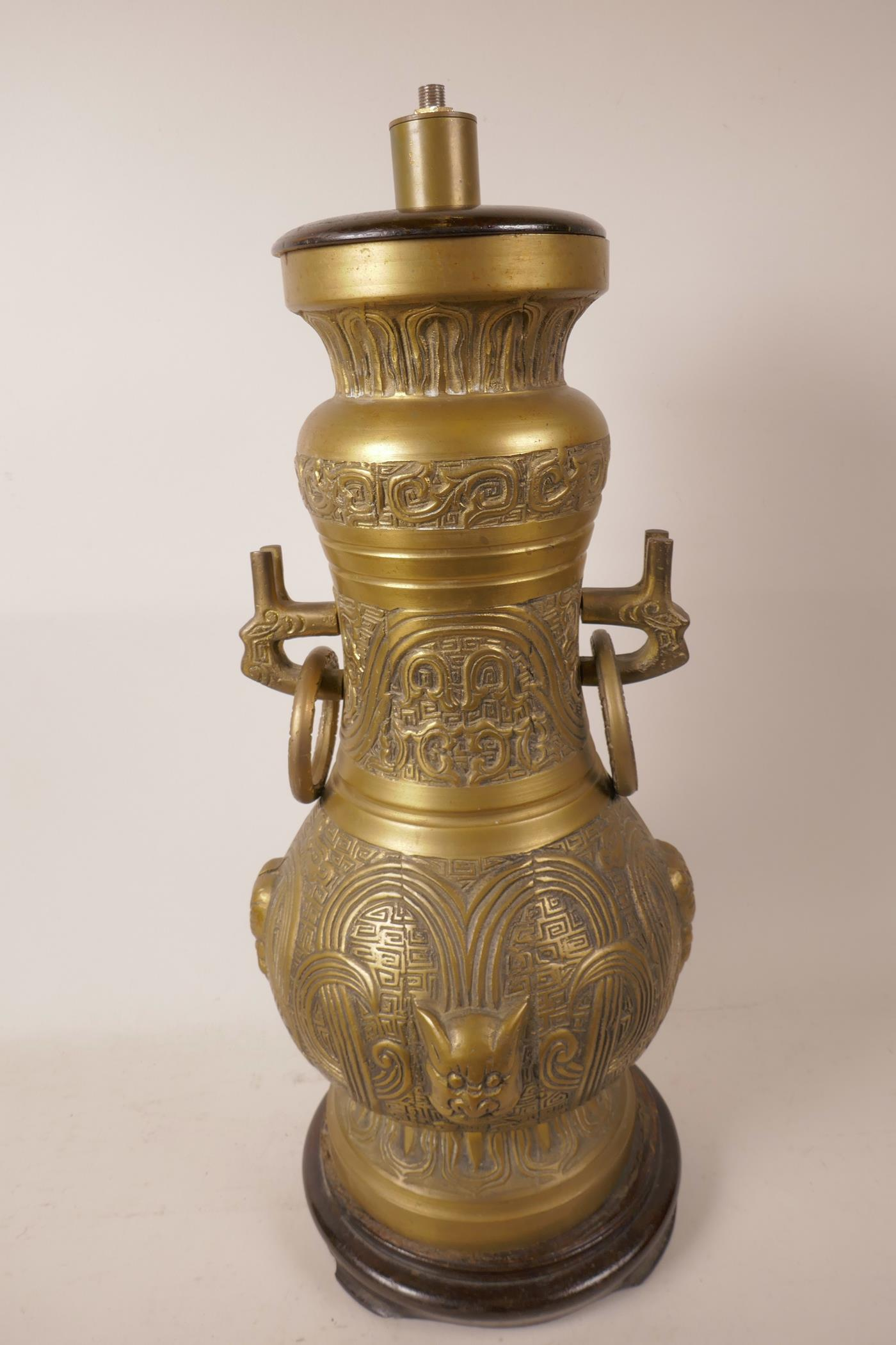 """Lot 372 - An Oriental bronzed metal table lamp cast with scrolls and masks, mounted on a turned wood base, 20"""""""
