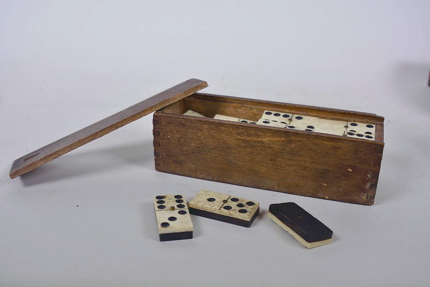 Lot 7 - A box of vintage games including two dyed bone part chess sets, crib board and dominoes