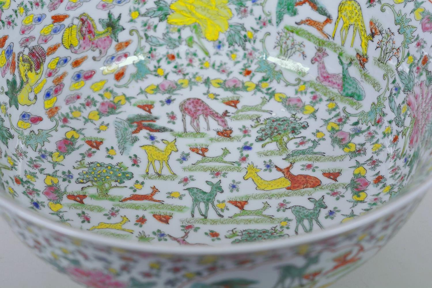 Lot 21 - A large Chinese porcelain bowl decorated with deer, mythical beasts and flowers in bright enamels,