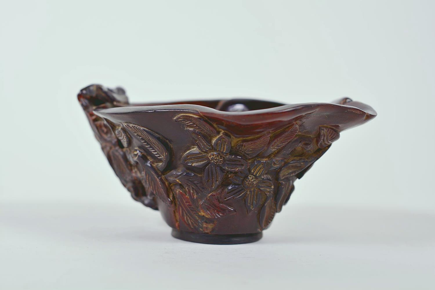 "Lot 15 - A Chinese faux horn libation cup with carved floral decoration, chased mark to base, 4½"" x 6"""