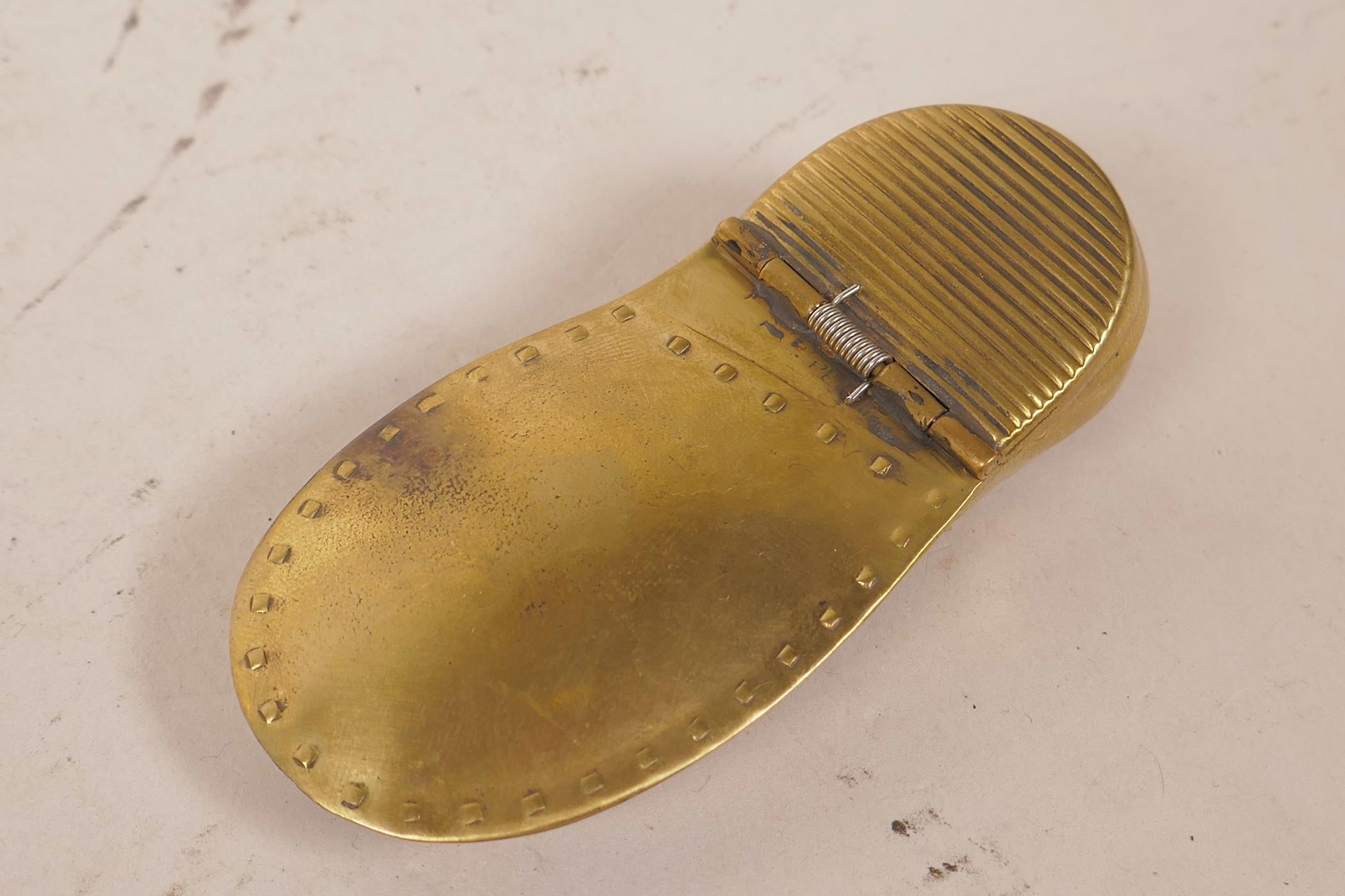 """Lot 22 - A novelty brass vesta case in the form of a lady's shoe within a shoe, 3"""" long"""