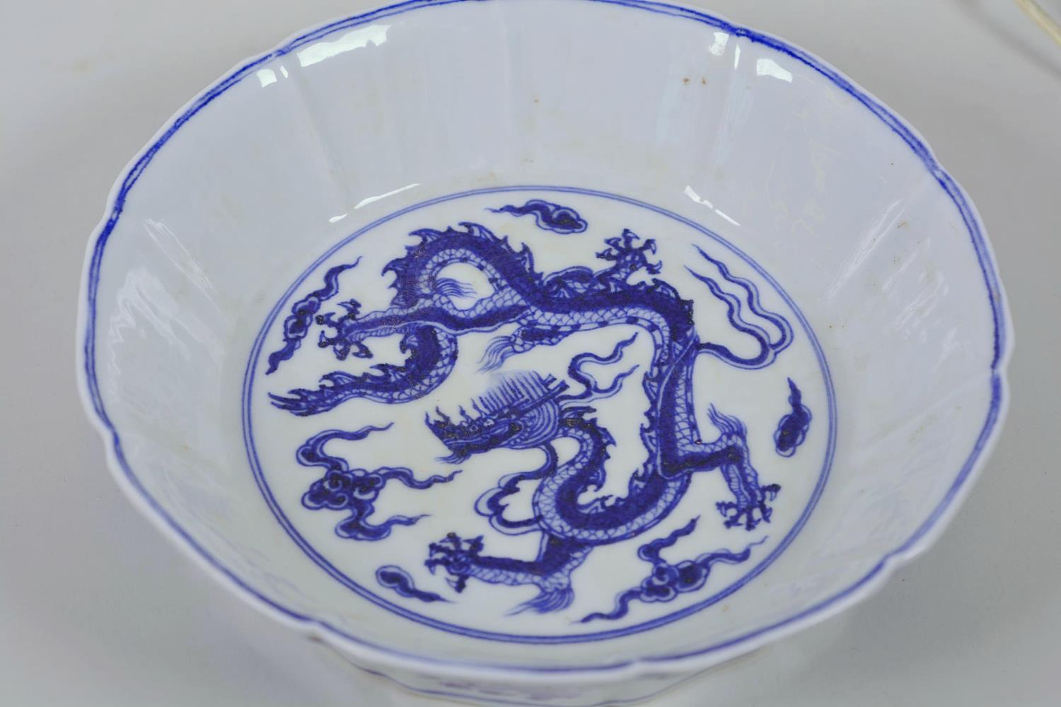 Lot 25 - A Chinese Ming style blue and white porcelain dish with lobed sides and dragon decoration, 6