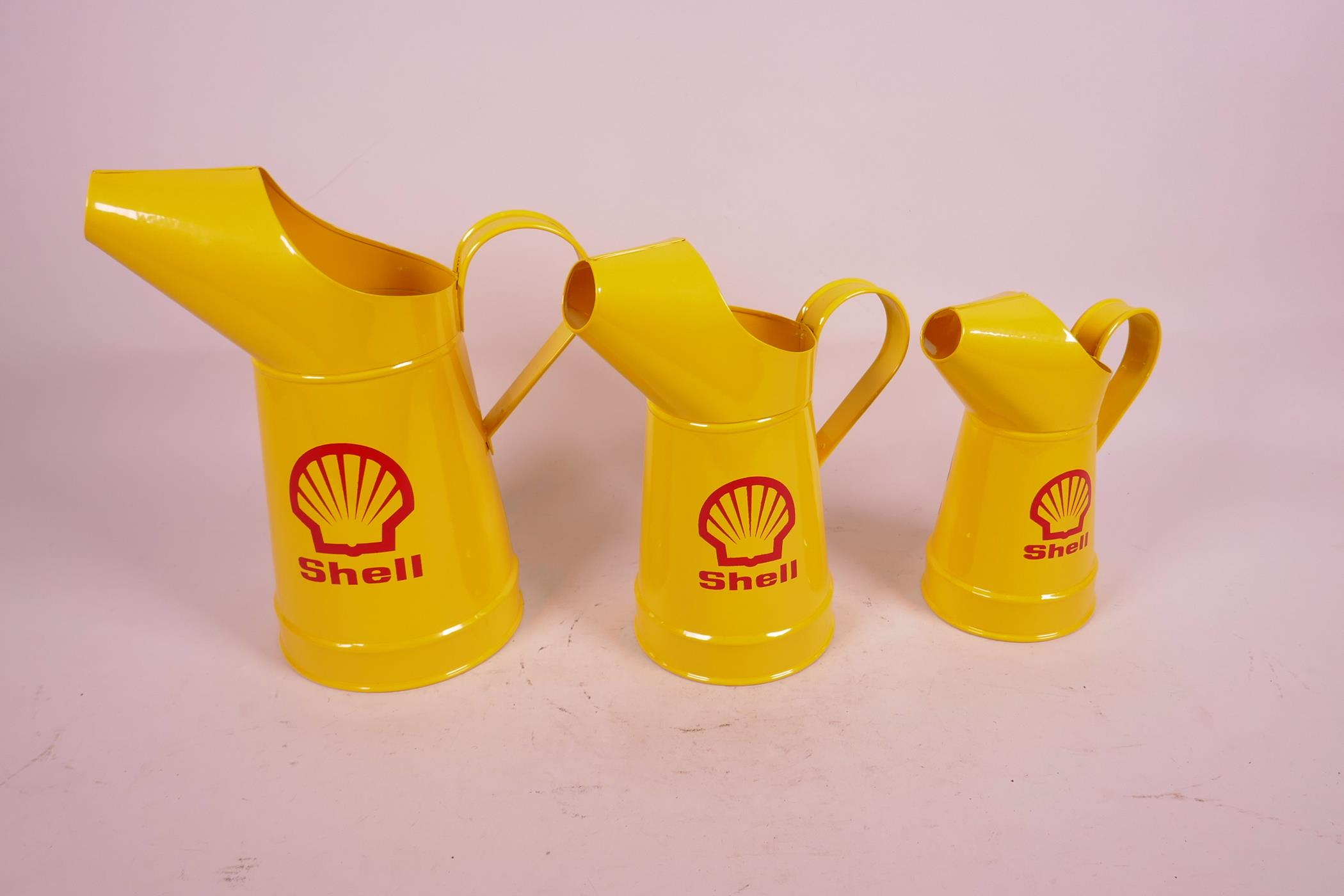 """Lot 2 - A set of three replica oil jugs decorated with the Shell logo, largest 10"""" high"""