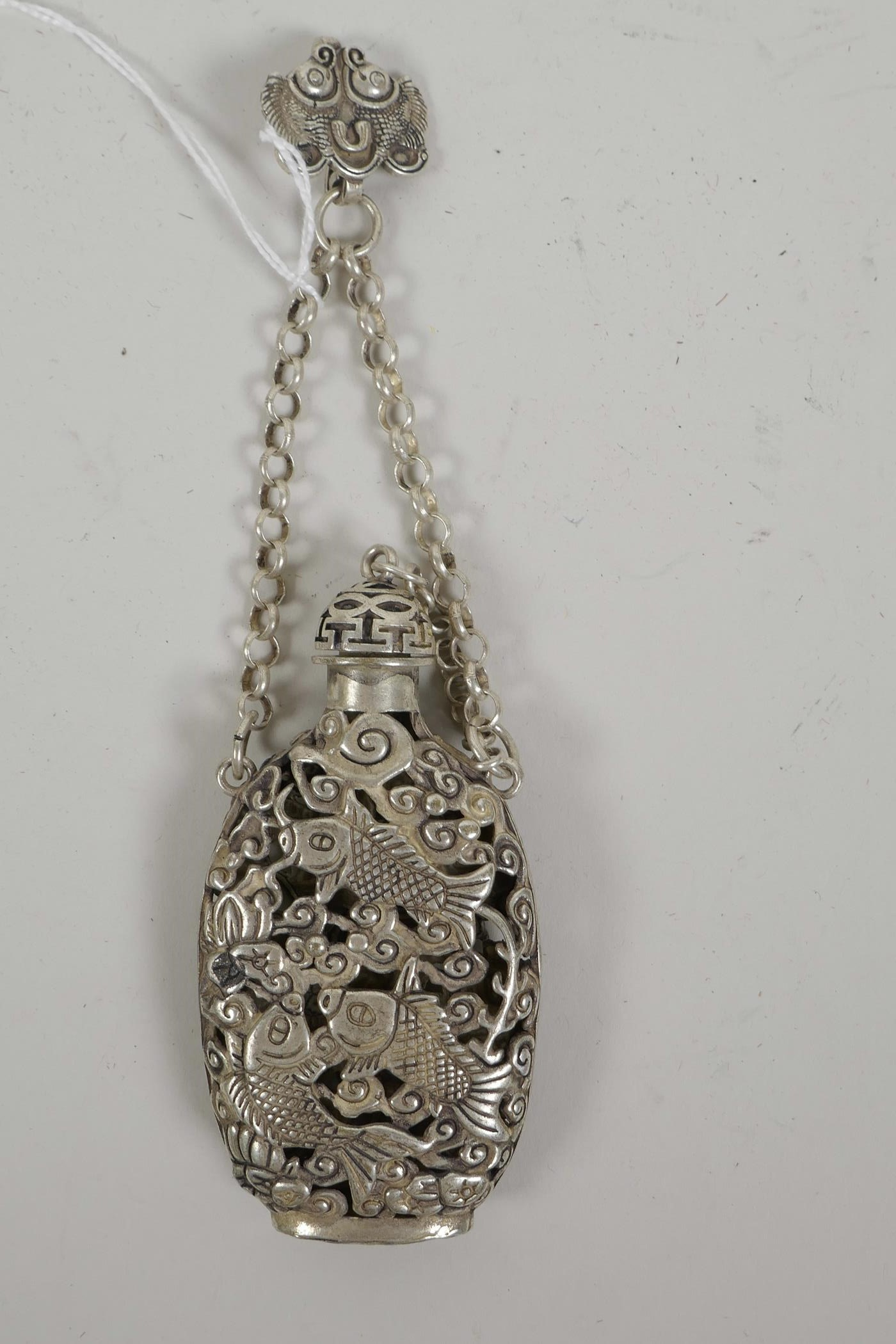 """Lot 5 - A Chinese white metal scent holder with pierced decoration of carp and lotus flowers, 6½"""" drop, mark"""