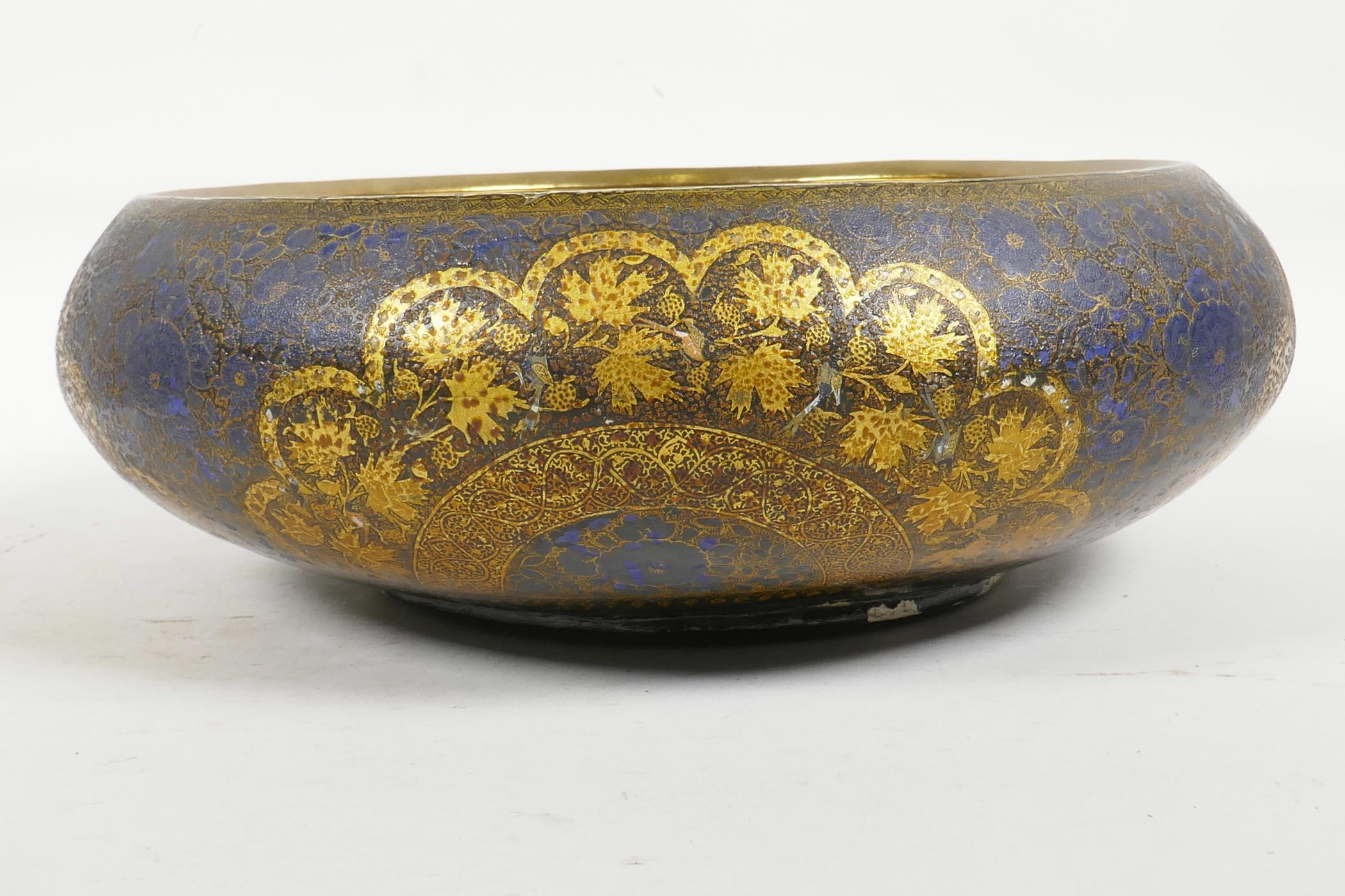 Lot 26 - A Kashmiri brass and lacquer bowl with a rolled rim, decorated with gilt floral patterns, signed