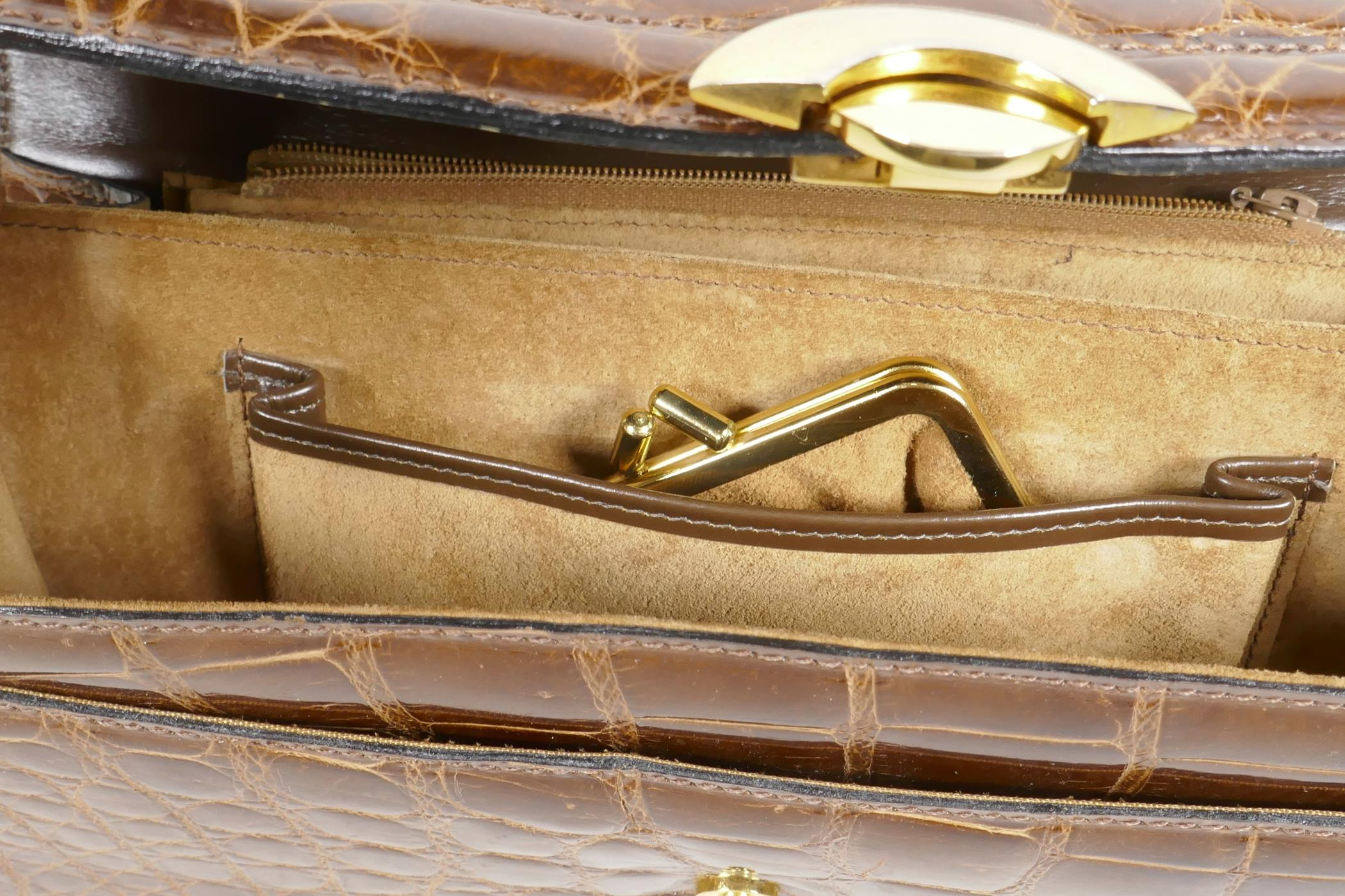"""Lot 15 - A crocodile skin handbag with brass fittings and shoulder strap, 10"""" x 6½"""""""
