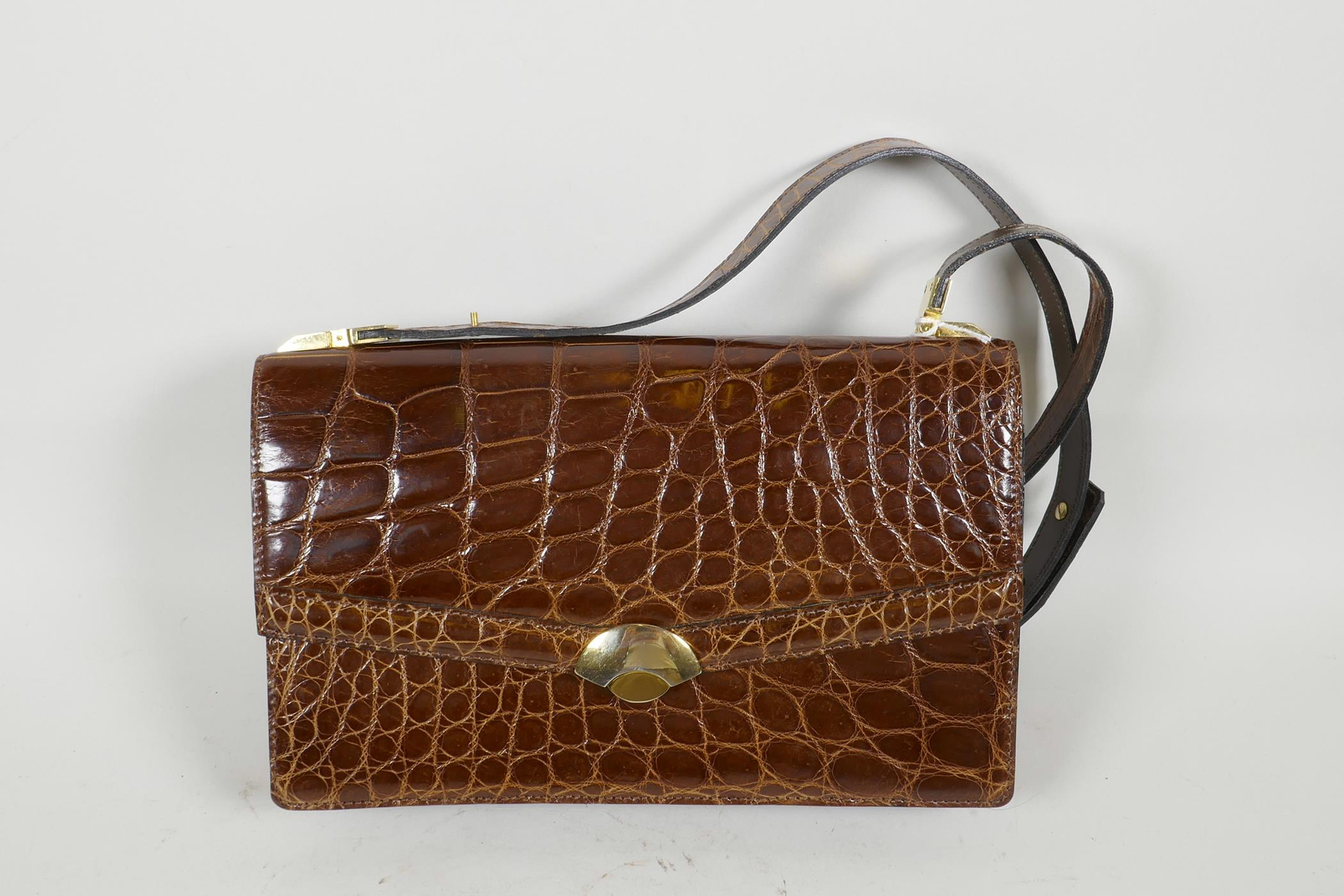 "Lot 15 - A crocodile skin handbag with brass fittings and shoulder strap, 10"" x 6½"""