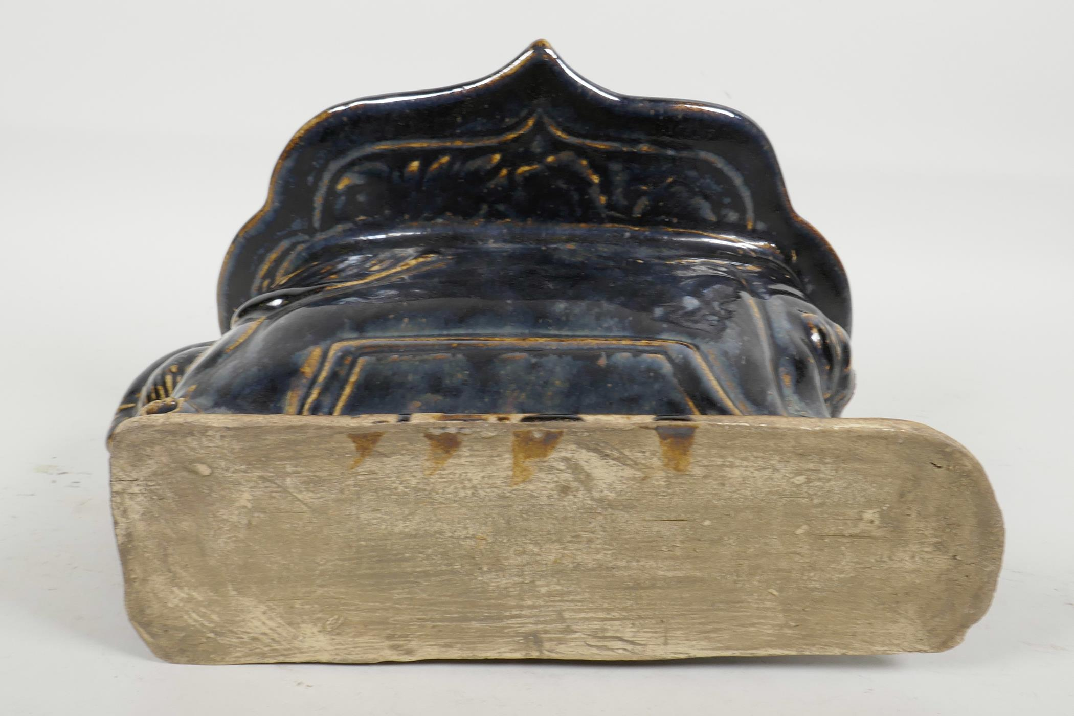 Lot 27 - A Chinese Cizhou kiln pottery head rest moulded in the form of a reclining figure, with blue black