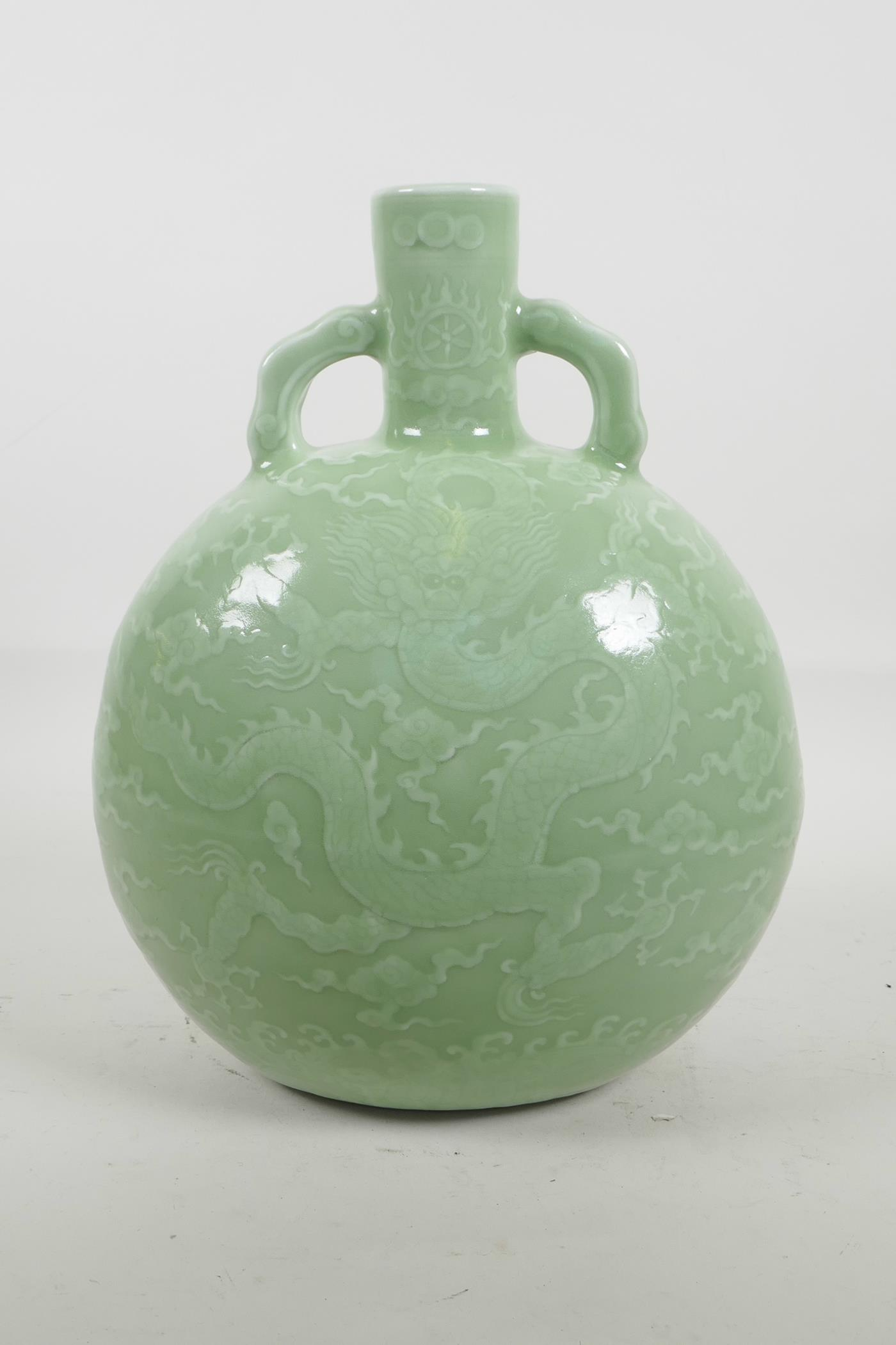 Lot 38 - A Chinese celadon glazed porcelain moon flask with two handles, with underglaze dragon decoration,
