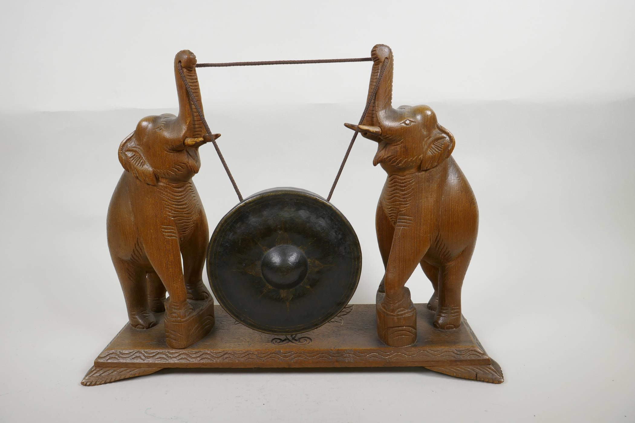 """Lot 26 - A bronze dinner gong, the wooden stand carved as two elephants with raised trunks, 13"""" high, 17"""""""