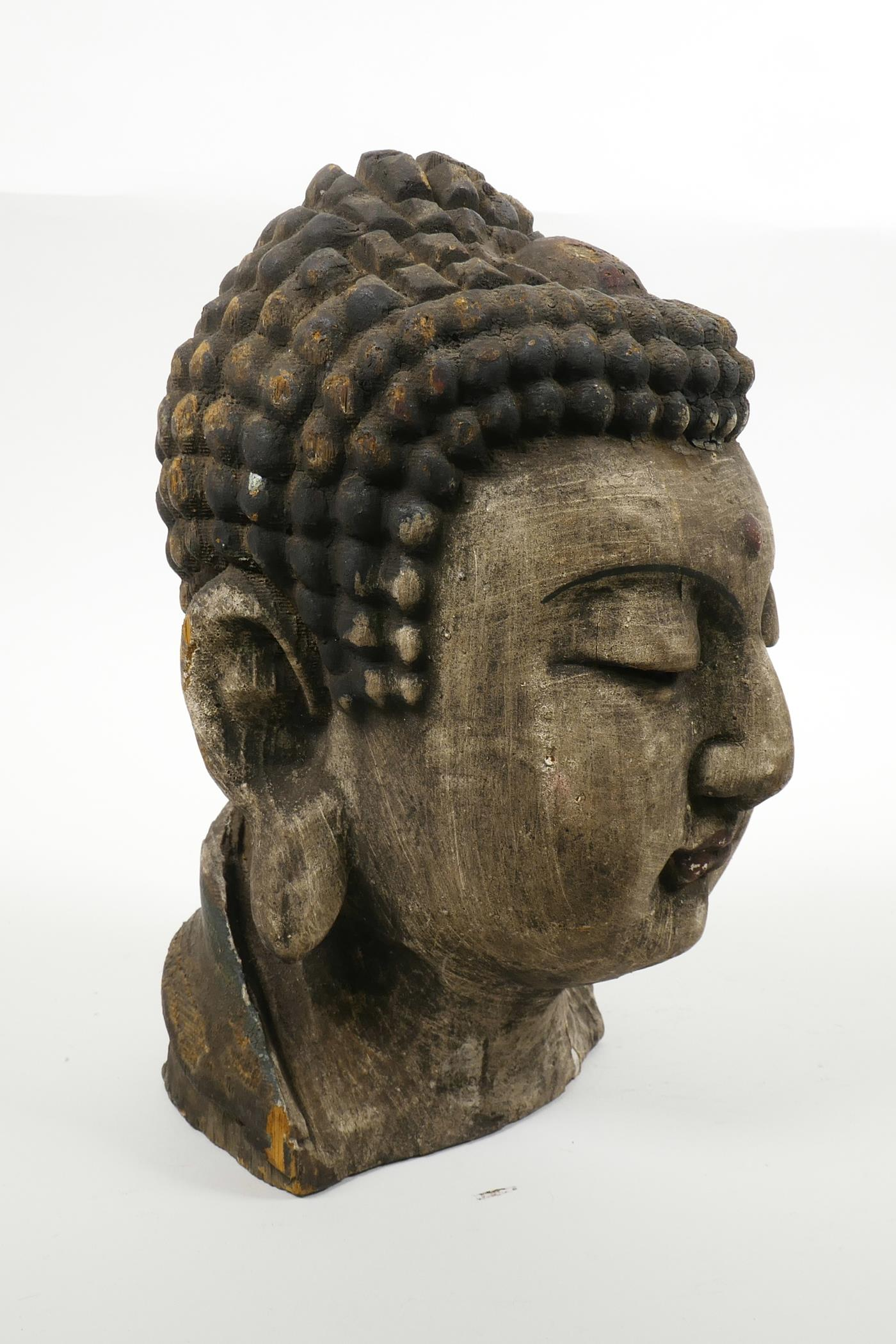 """Lot 35 - An oriental carved and painted Buddha head, 9½"""" high"""