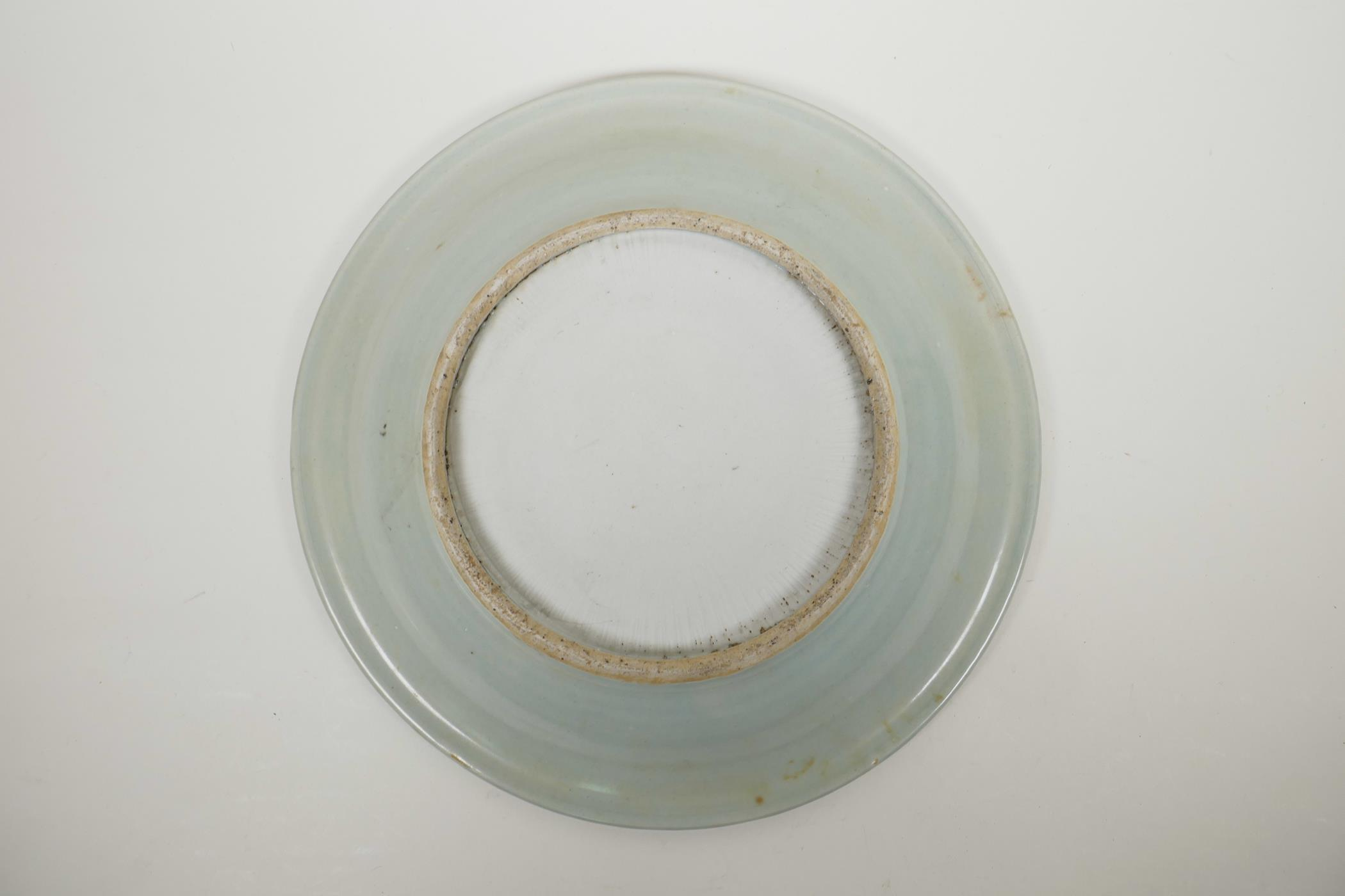 Lot 65 - A Chinese celadon glazed porcelain charger with incised decoration of a warrior and four