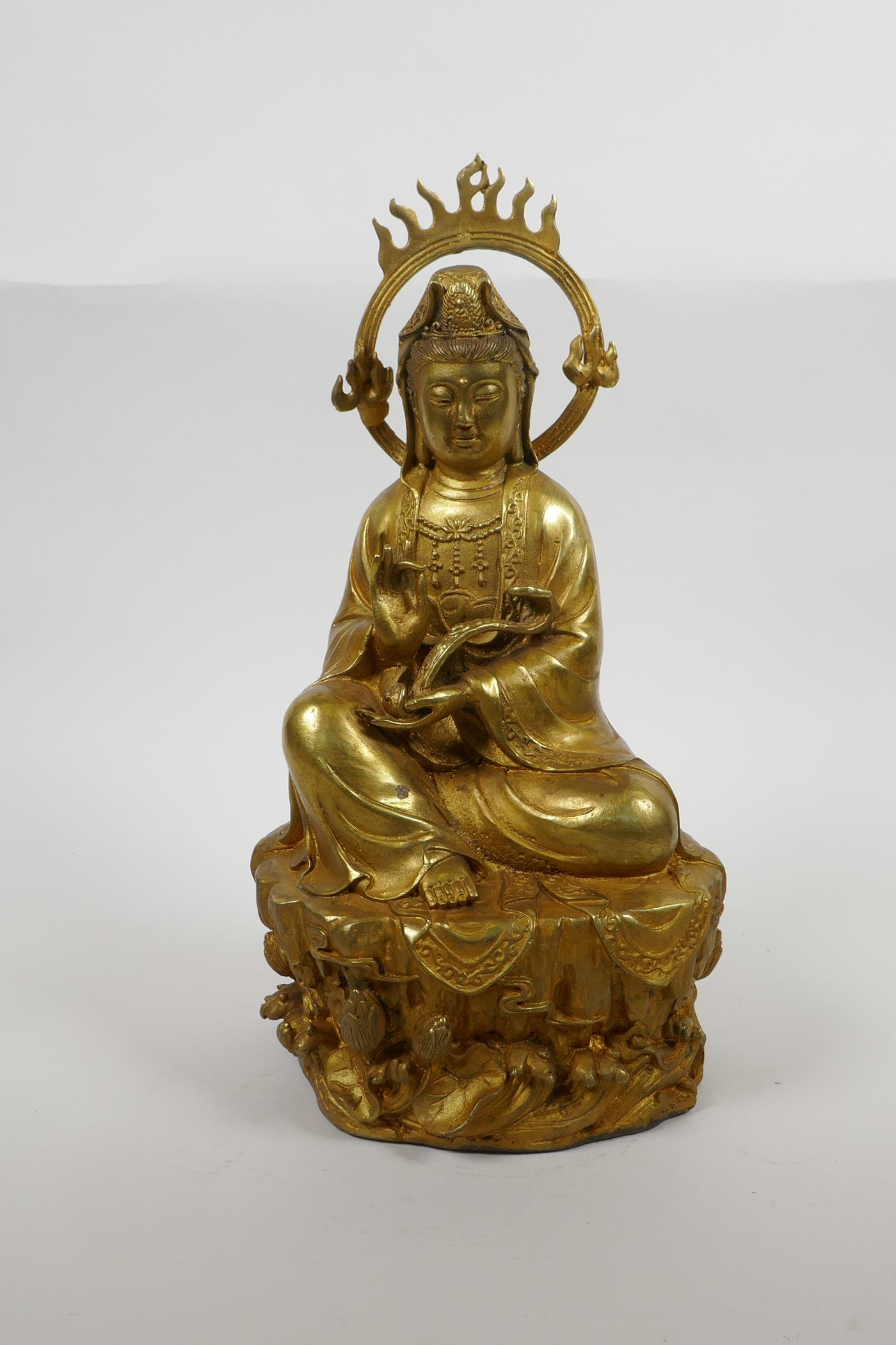 """Lot 38 - A Chinese gilt bronze of Quan Yin seated on a lotus throne, 12"""" high, A/F crack to halo"""