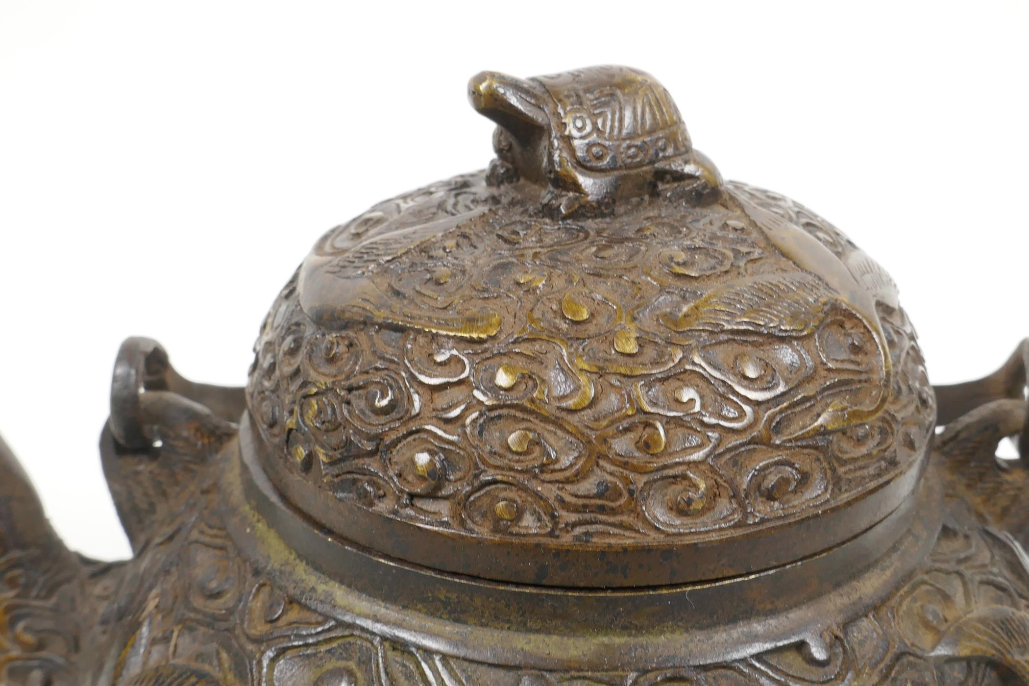 """Lot 18 - A Chinese bronze teapot with raised decoration of cranes in flight, four character mark to base, 5½"""""""