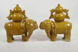 """A pair of Chinese ochre glazed porcelain elephants carrying double gourds, 10"""" high"""