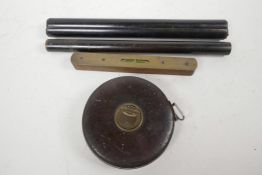 A vintage Chesterman leather cased steel bladed surveyor's tape, together with an ebonised desk rule