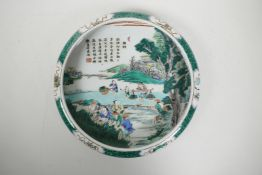 A Chinese famille verte porcelain dish with a rolled rim, decorated with figures in a rice paddy, Ka
