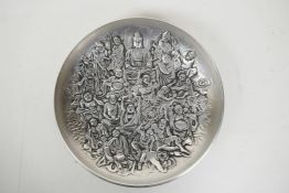 A Chinese white metal dish with raised decoration of Buddha and other deities, impressed seal mark t