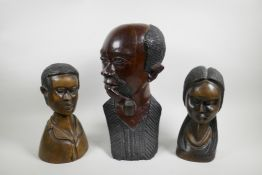 An African carved wood bust of a pipe smoking gentleman together with a pair of carved hardwood bust