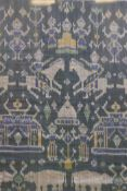 """A framed Indonesian green ikat textile depicting figures, animals and temples, 36"""" x 39"""""""