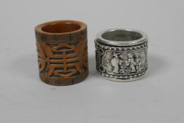 A Chinese white metal archer's thumb ring with a revolving cuff, together with a carved thumb ring