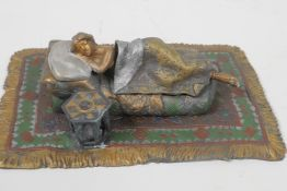 """A cold painted bronze figure of a girl lying on a bed, 6¼"""" long"""