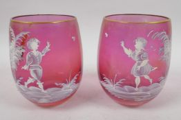 A pair of cranberry glass tumblers with Mary Gregory style decoration of young children and a