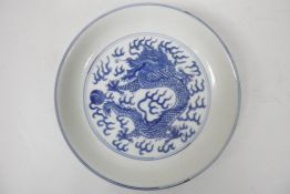 A Chinese blue and white porcelain cabinet dish decorated with a dragon chasing the flaming pearl,